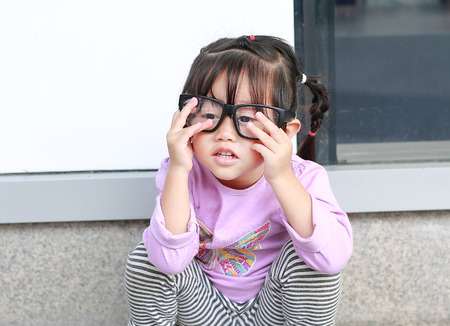 Portrait of cute little girl trying to wear glasses