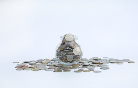 Overflowing jar of International coins on white background with copy space.