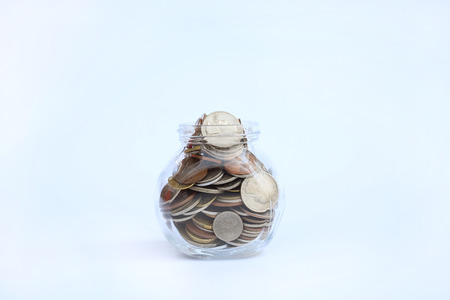 International coins in a glass jar on white background