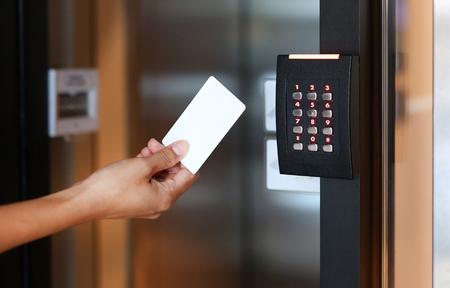 Controle de acesso de porta - jovem mulher segurando um cartão-chave para bloquear e destravar a porta. Foto de archivo