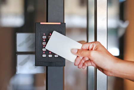 Door access control - young woman holding a key card to lock and unlock door. Zdjęcie Seryjne - 90938427