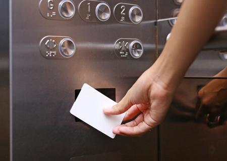 lifttoegangscontrole, hand met een sleutelkaart om de liftvloer vóór of naar boven te ontgrendelen Stockfoto