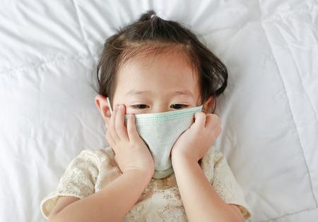 Petite fille asiatique portant un masque de protection couché sur le lit. Banque d'images - 91164322