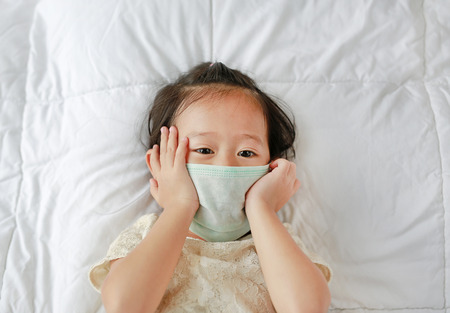 Asian little girl wearing a protective mask lying on the bed.