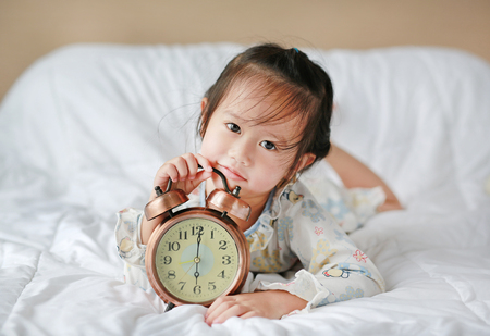 Happy beautiful girl with alarm clock on bed