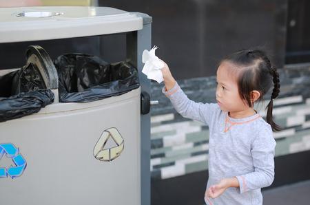 Cute little girl putting waste in the bin outdoor