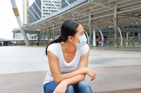 Woman wearing protective mask to protect pollution and the flu sitting at public area. Stock Photo