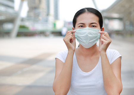 Person wearing protective mask to protect pollution and the flu sitting at public area. 免版税图像 - 92538079