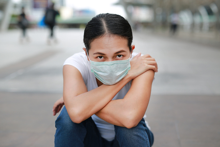 Woman wearing protective mask to protect pollution and the flu sitting at public area. Foto de archivo