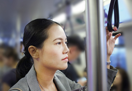 Young asian woman inside BTS (Bangkok Mass Transit System), the public transportation in Bangkok, Thailand.