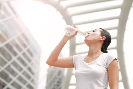 Thirsty woman drinking water in public area.