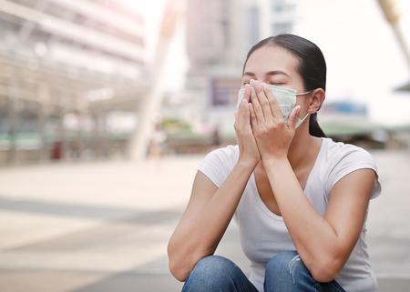 公害や公共エリアに座っているインフルエンザを保護するために保護マスクを着用している女性。
