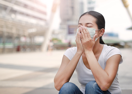Woman wearing protective mask to protect pollution and the flu sitting at public area. Stockfoto