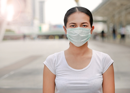 Woman wearing protective mask to protect pollution and the flu standing at public area.