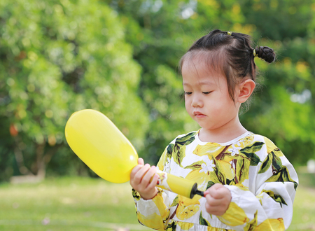 Cute little girl using plastic air pump balloon in the park on a sunny day.