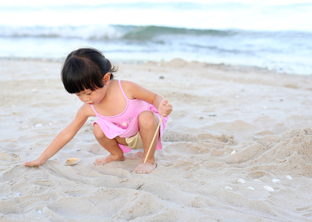 Portrait Kid girl playing sand at the beach