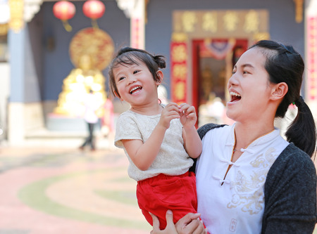 Portrait of mother and cute little girl at chinese temple in Yaowarat Road (Bangkok chinatown) at Chinese new year, Bangkok Thailand.