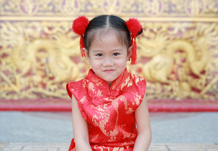 Smiling little asian girl in cheongsam on traditional chinese new year festival.