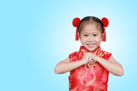 Happy little Asian child girl wearing red cheongsam with greeting gesture celebration for Chinese New Year isolated on cyan background.