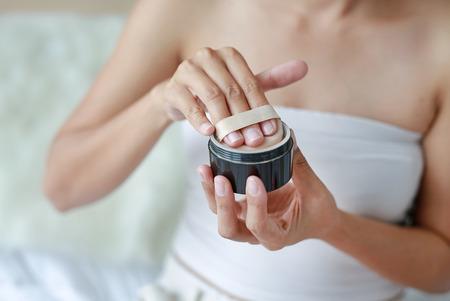 Beauty asian woman applying makeup with Sponge Powder Puff. Woman make up herself.