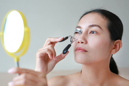 Portrait of beautiful woman making curl eyelashes. Beautiful woman face.