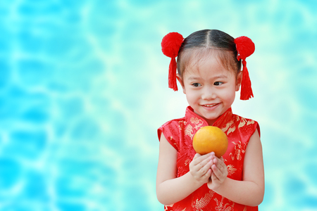 Cute asian kid girl in Traditional Chinese dress with holding sacred Orange isolated on cyan background, Chinese new year concept.