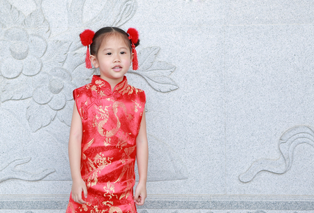 Little asian girl in cheongsam on traditional chinese new year festival.