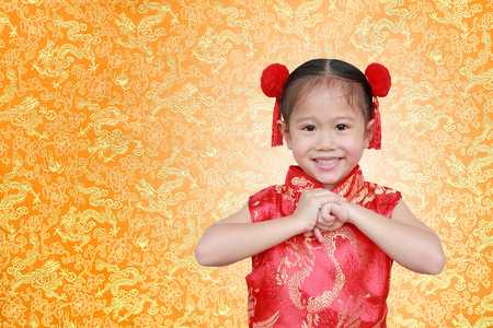 Asian girl in Cheongsam respecting on traditional Chinese new year festival on Chinese background. Stock Photo