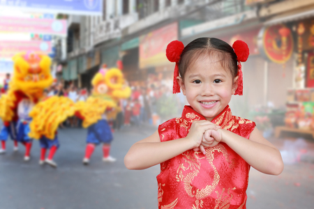 Little chinese girl in traditional Chinese cheongsam blessing for you in chinese new year festival.