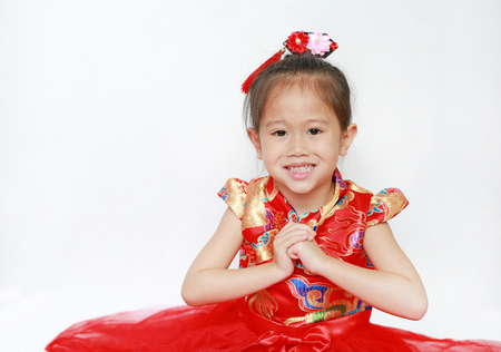 Happy little Asian child girl wearing red cheongsam with greeting gesture celebration for Chinese New Year isolated on white background. Stock Photo