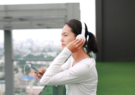 Young asian woman listening music in headphones at rooftop of the building