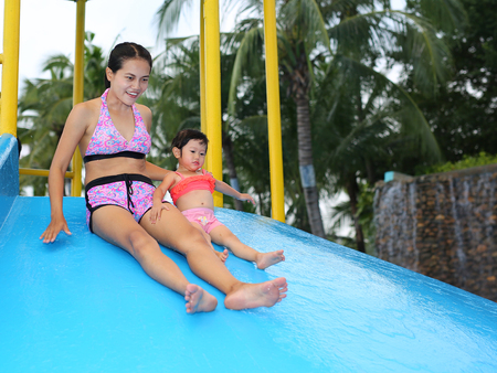 Pretty little girl with her mother sliding in swimming pool outdoors Stock Photo
