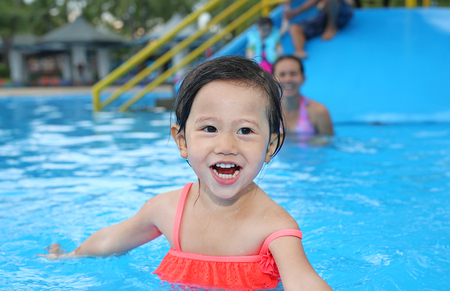 Pretty little girl playing in swimming pool outdoors