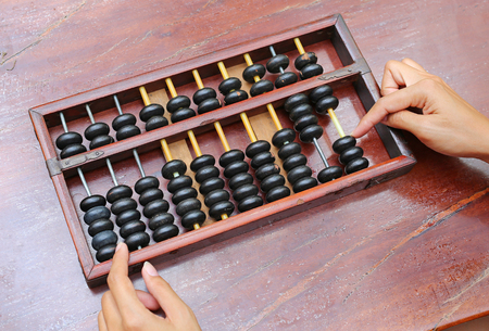 Woman hands using Chinese ABACUS old antique calculator retro finance education, tool work business accounting