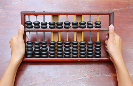 Woman hands holding Chinese ABACUS old antique calculator retro finance education, tool work business accounting