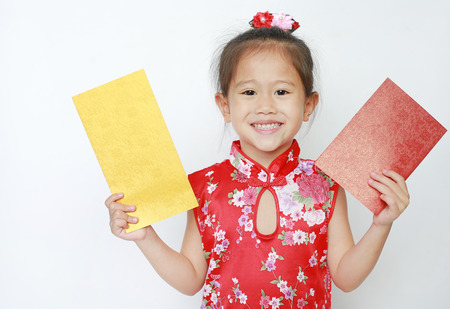 Happy little Asian child girl holding gold and red envelope on white background