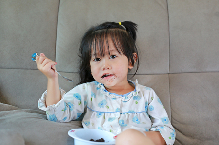 Little child girl in pajamas eating with dirty mouse