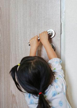 Little child girl try to open locked door, Little child hand on the door handle