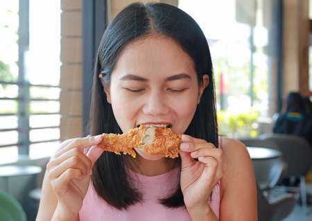 Close up of young asian woman eating fried chicken in cafe.