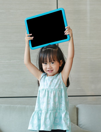 Cute little child girl holding empty blackboard standing on fabric sofa in library room. Education concept.