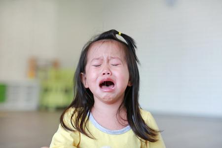 Close-up Klein kind meisje huilen met betraand op haar gezicht.