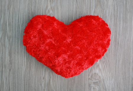 Red heart pillow on wood background