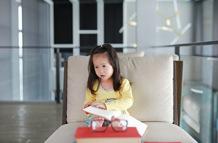 Little child girl reading book in library, Education concept.