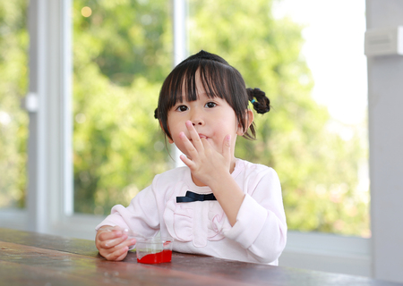 Adorable Little asian girl sucking finger in mouth.