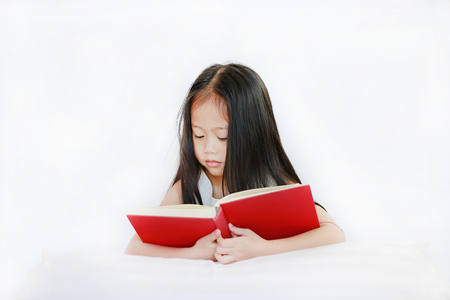 Beautiful little Asian child girl reading hardcover book lying with pillow on white background Stock fotó