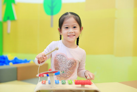 Asian kid girl having fun with Toys, musical instruments