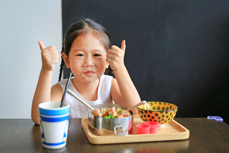 Happy little Asian kid girl eating rice by self in the restaurant