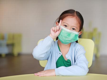 Linda niña asiática con una máscara protectora mostrando un dedo índice sentado en una silla para niños en la habitación de los niños