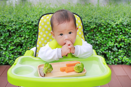 Asian infant baby boy eating by Baby Led Weaning (BLW). Finger foods concept Foto de archivo