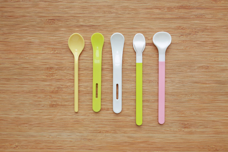 Different type of plastic spoons for babies on wood board background